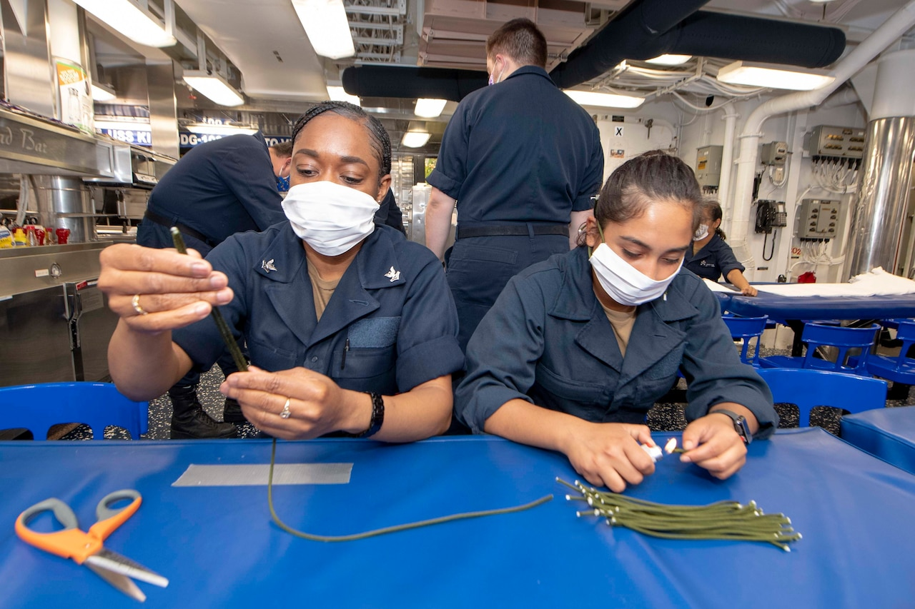 Sailors cut paracord to make straps for face masks.