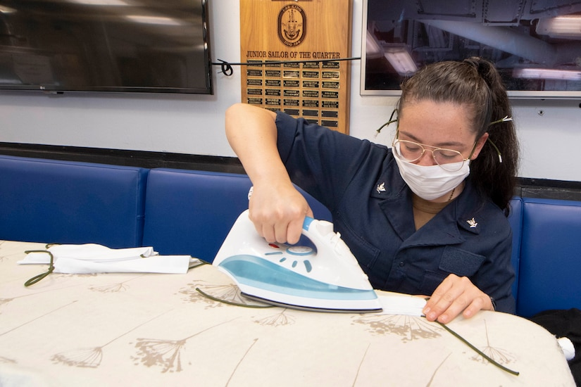 A sailor irons fabric used to make face masks.