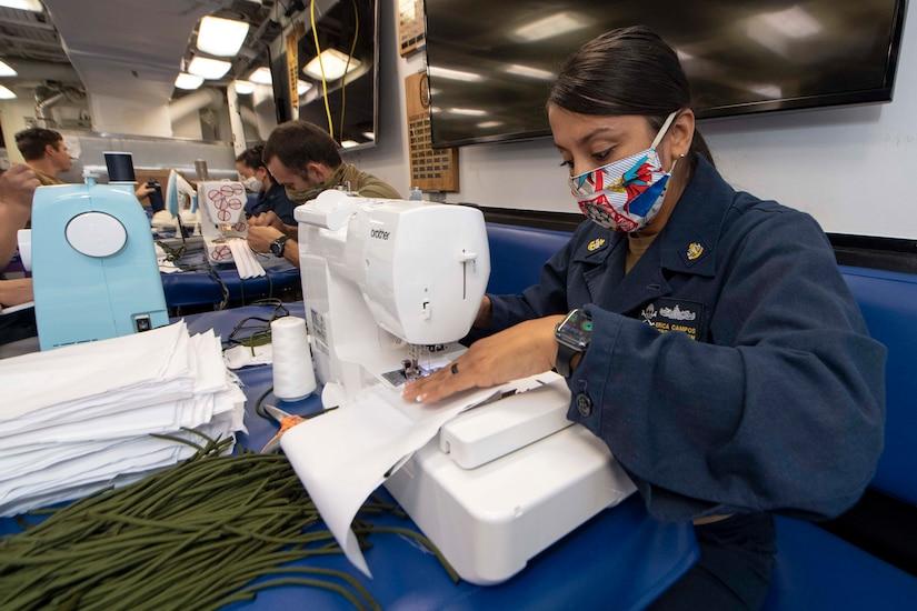 A Navy chief sews face masks.