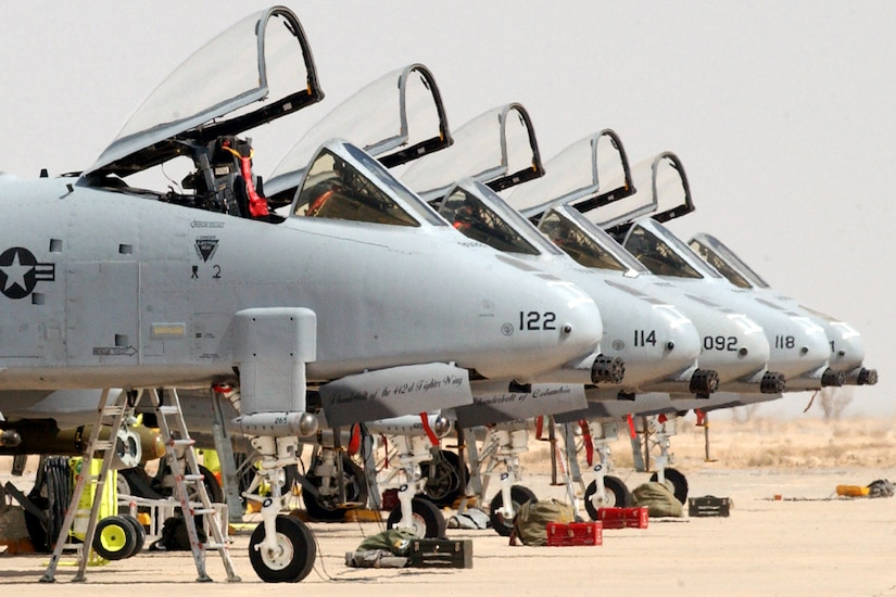 Five A-10 aircraft line up beside each other on the tarmac with their cockpits open. No pilots are in them.