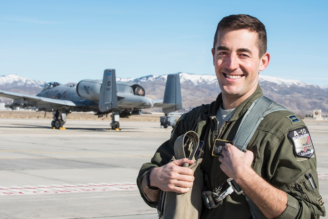 An A-10 pilot wearing a flight suit poses for a photo with an A-10 aircraft on the tarmac behind him and mountains in the background.