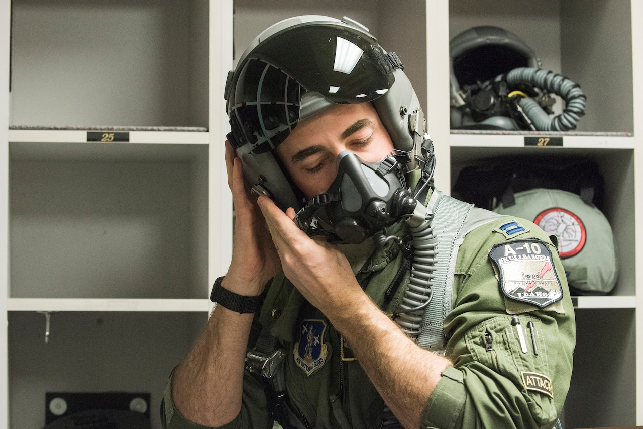A pilot in a flight suit latches his flight helmet to his head.