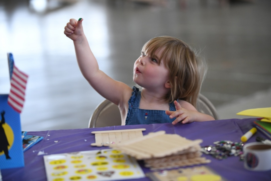 Shannon Cross, the daughter of Tech. Sgt. James Cross, a 34th Aircraft Maintenance Unit flight line expeditor, creates a picture frame at the arts and crafts table, during the Back to School Roundup held at the Pride Hangar on Ellsworth Air Force Base, S.D., Aug. 18, 2019. April has been designated as the Month of the Military Child. It is set aside to honor the strength and sacrifices of military children across all branches. (U.S. Air Force photo by Airman 1st Class Christina Bennett)
