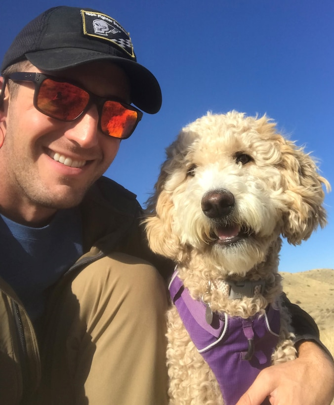 A man in sunglasses and ball cap kneels to take a selfie with his fluffy golden-colored dog.