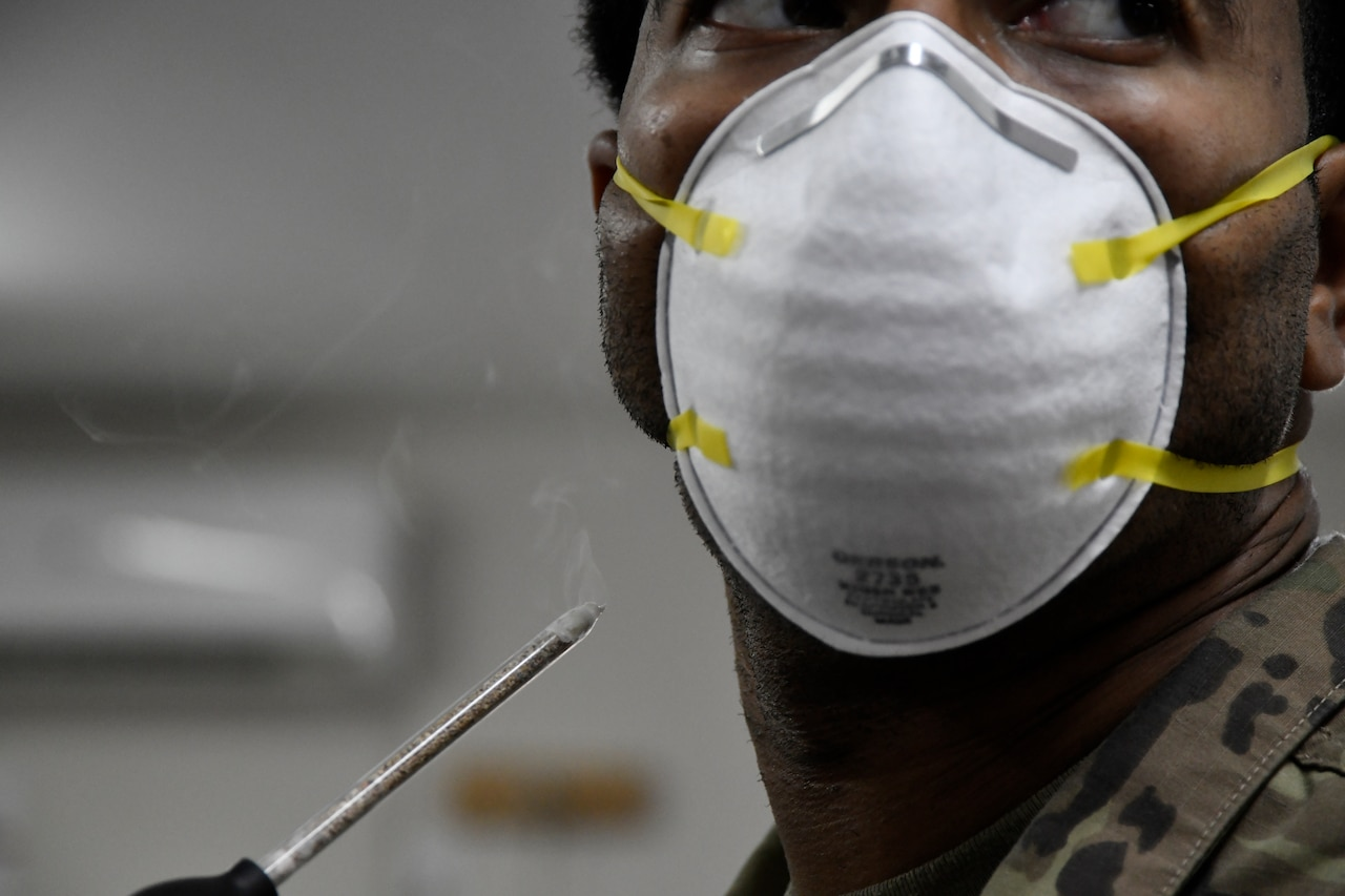 A service member wears a face mask as he holds a device that generates smoke.