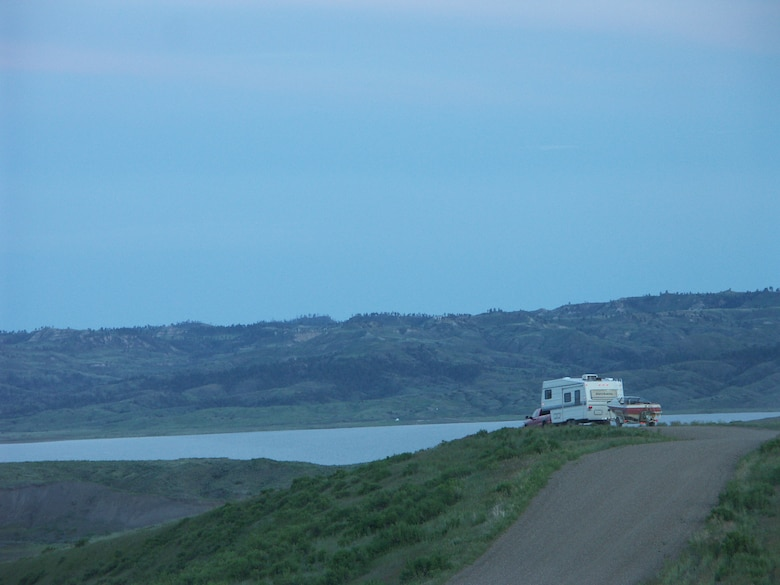 Camper with boat driving into Fourchette Bay on Fort Peck Lake