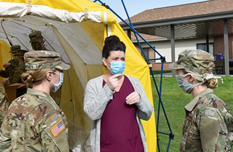 Wisconsin National Guard Soldiers and Airmen talk with a staff member of the Orchard Manor long-term care facility in Lancaster April 25, 2020, about the importance of safely collecting specimens to test residents and staff  for COVID-19.