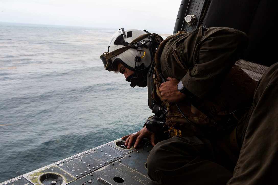 Naval Air Crewman 2nd Class Joseph Rivera, a search and rescue swimmer assigned to the amphibious assault ship USS Makin Island, looks out of a U.S. Navy MH-60 Seahawk while conducting search and rescue relief operations following an AAV-P7/A1 assault amphibious vehicle mishap off the coast of Southern California, July 30, 2020. Assisting in the search and rescue relief operations are the guided-missile destroyer USS John Finn, multiple U.S. Navy MH-60 helicopters and small boats from USS Makin Island, the amphibious transport dock USS Somerset, the amphibious transport dock USS San Diego, as well as the U.S. Coast Guard Cutter Forrest Rednour and a Coast Guard MH-60 Jayhawk helicopter from Coast Guard Sector San Diego.
