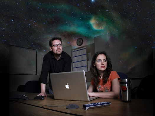 Mike Cushing and Amy Mainzer of JPL in a conference room at the California Institute of Technology in Pasadena. This is a dramatized image, enhanced with a starry sky, illustrating the mood during what astronomers call remote observing.