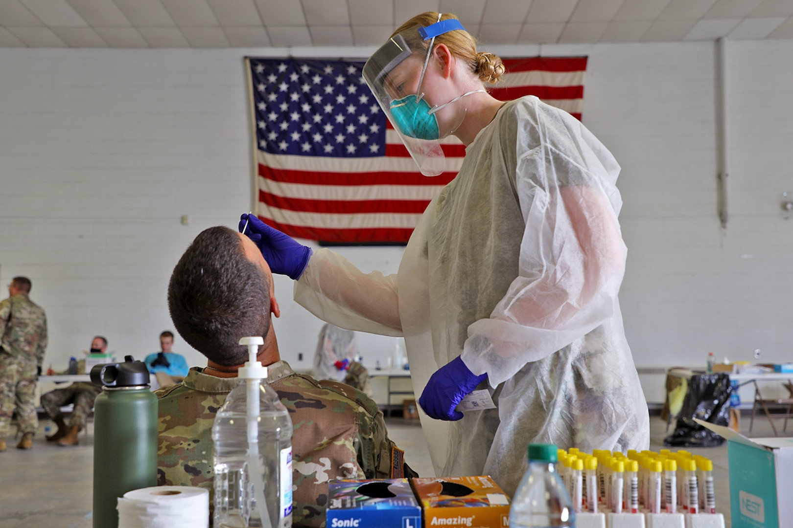 Female in white gown and blue gloves, clear face shield inserts a tester into a male soldier's nose to test for the coronavirus.
