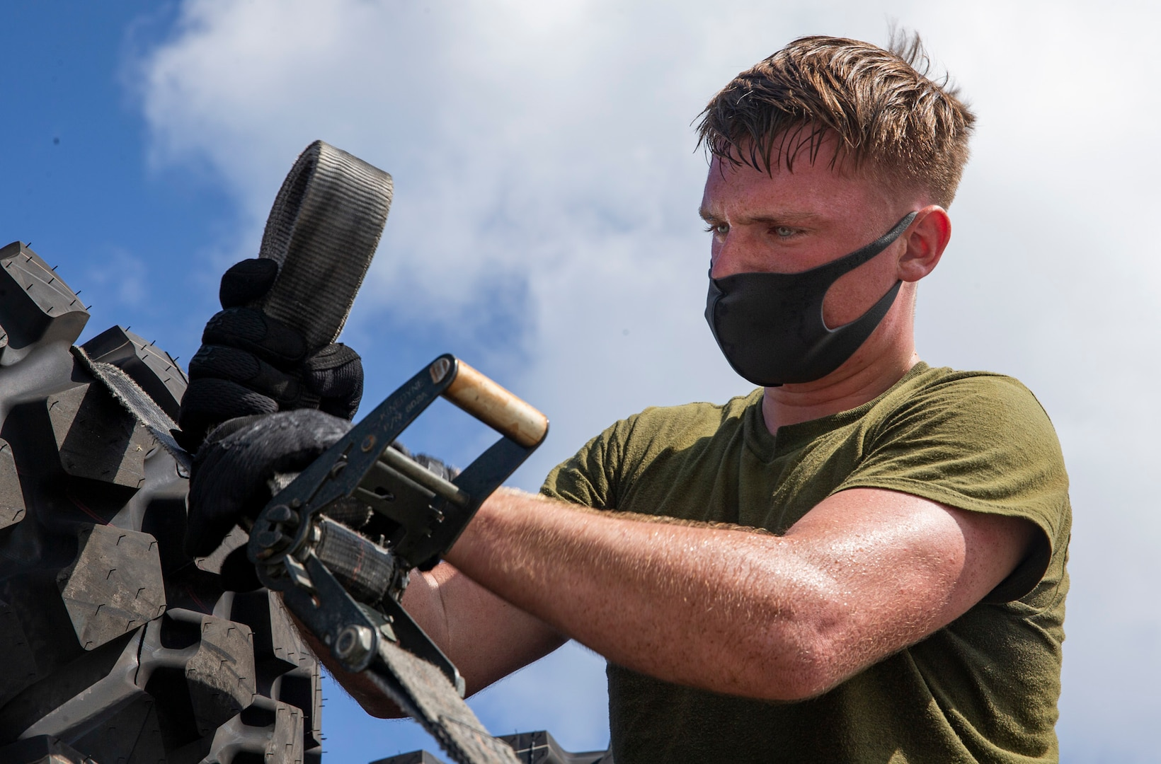 Male wearing a face mask works on a piece of equipment outdoors.