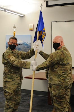 Col. Jordan Murphy, 302nd Maintenance Group commander, passes the 302nd Aircraft Maintenance Squadron guidon to Lt. Col. Cody Whittington during a change of command ceremony.