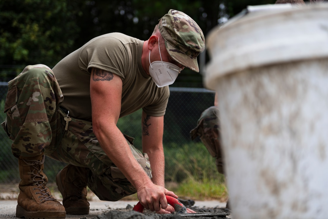 A photo of an Airman demonstrating appropriate procedure for finishing concrete.