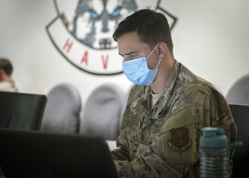 An airman wearing a face mask works at a computer.
