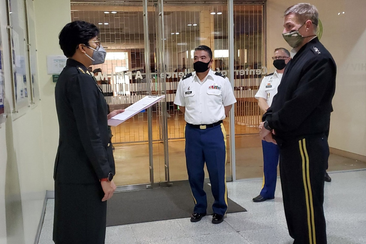 A female officer and a male officer face each other to talk as two other service members look on. All are wearing face masks.
