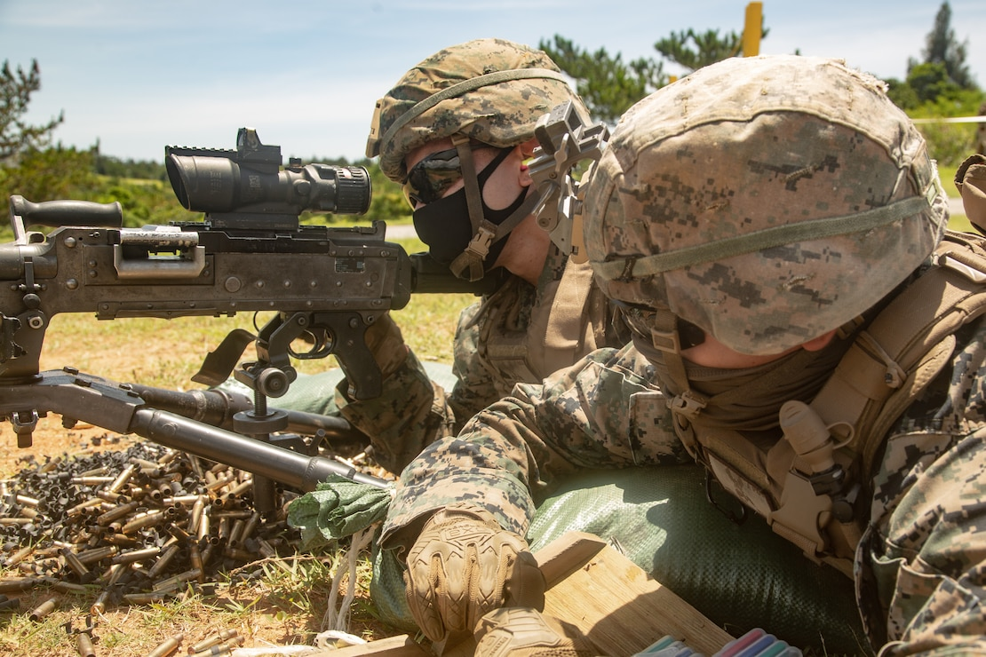 U.S. Marines fire a M240 medium machine gun during a live fire range at Camp Hansen, Okinawa, Japan, July 23.
