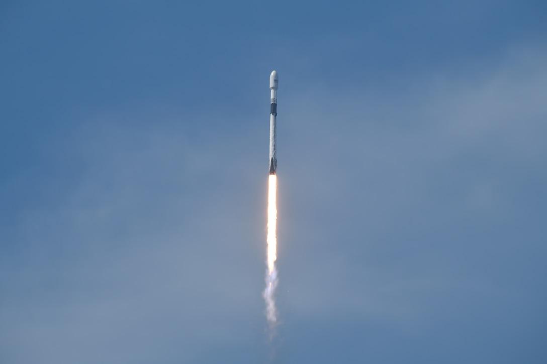 A rocket travels through a blue sky.