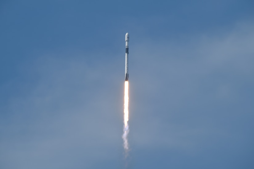 A rocket travels through a blue sky.