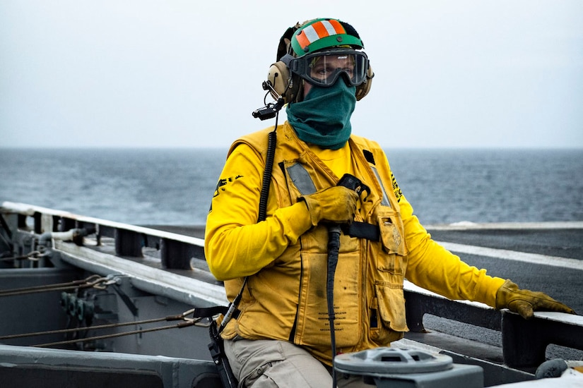 A sailor stands on the deck of a ship.