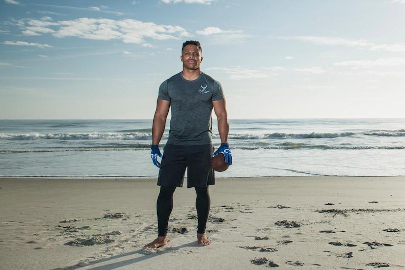 A man holding a football stands on a beach.