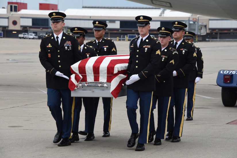 National Guardsmen carry a casket draped in an American Flag.
