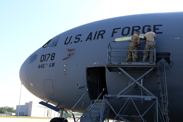 Master Sgt. Toron Franklin, aircraft mechanic and crew chief with the 445th Maintenance Group, installs a new electroluminescent panel on the Wright Patterson Air Force Base, Ohio, flightline, July 19, 2020. The electroluminescent panel glows green when in use. When connected to an alternating current/direct current source, this panel emanates light from crystalline powders or phosphors that are sandwiched between electrically conductive surfaces, one of which is translucent. The powders absorb the electrical energy and convert it instantly into light with minimal heat. (U.S. Air Force photo/Senior Airman Amelia Burnett)