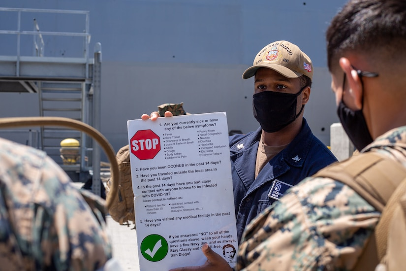 A sailor wearing a face mask holds a sign describing the symptoms of COVID-19.