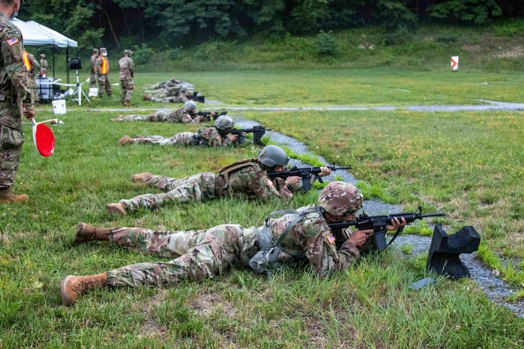 Guardsmen lay on the ground holding weapons.
