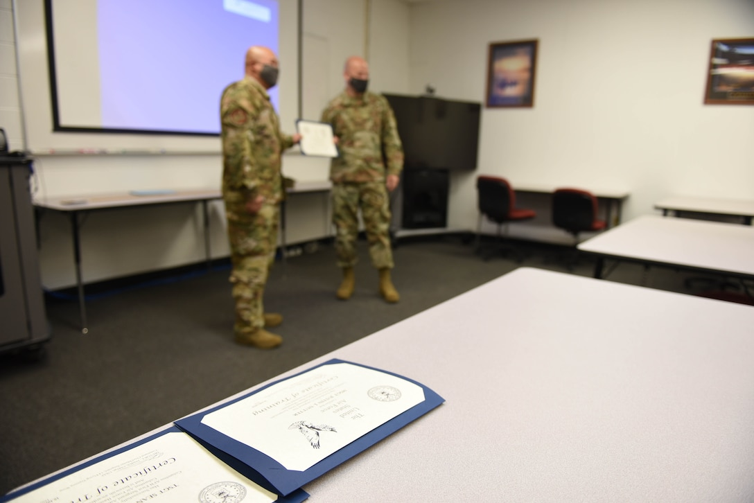 Tech. Sgt. Nazareth Oliver, 14th Operational Medical Readiness Squadron Aerospace and Operational Physiology Flight technician, receives his certification from Chief Master Sgt. Trevor James, 14th Flying Training Wing command chief July 16, 2020, after completing the Additional First Sergeant Symposium on Columbus Air Force Base, Miss. All of the curriculum for the symposium was given to the Columbus AFB First Sergeants running the program by the Air Force First Sergeant Academy. (U.S. Air Force photo by Senior Airman Keith Holcomb)