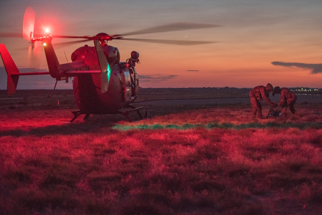 Soldiers work near a helicopter bathed in red light.