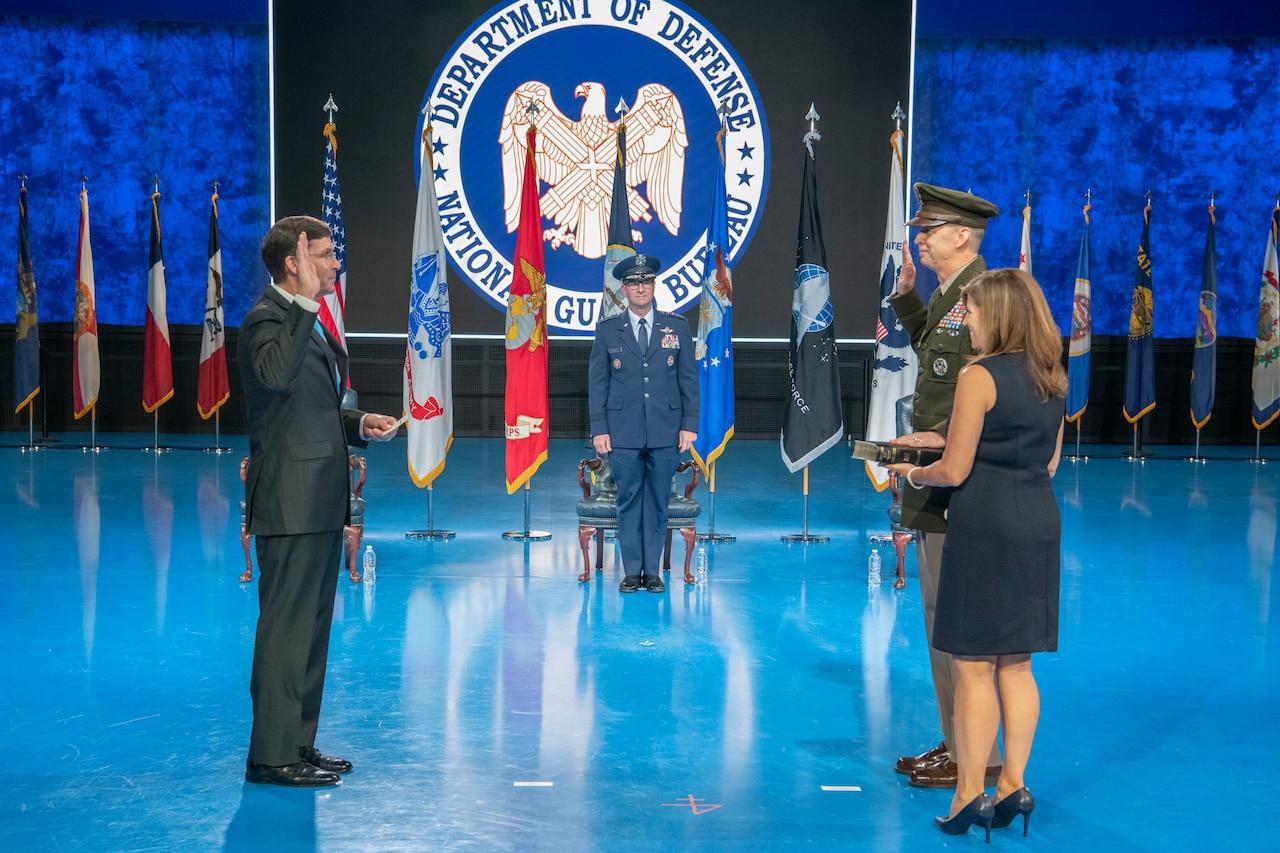 Defense Secretary Dr. Mark T. Esper holds up his right hand facing Army Lt. Gen. Daniel R. Hokanson who is also raising his right hand.