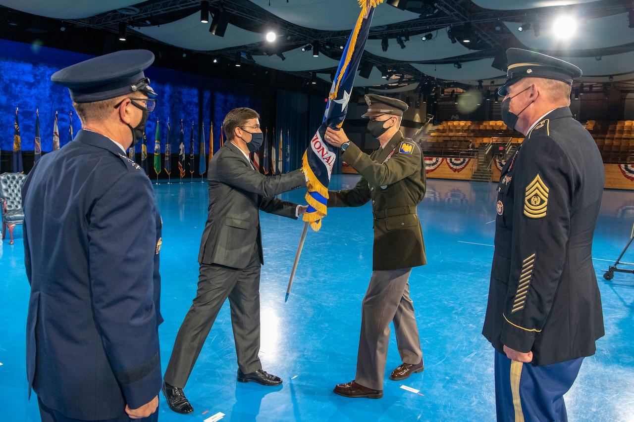 Defense Secretary Dr. Mark T. Esper hands a flag to Army Lt. Gen. Daniel R. Hokanson; others stand around.
