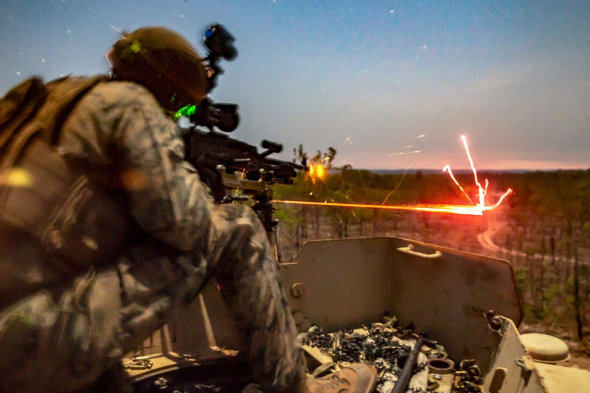 A line of red light shoots into a field as a Marine fires a weapon in low-light conditions.