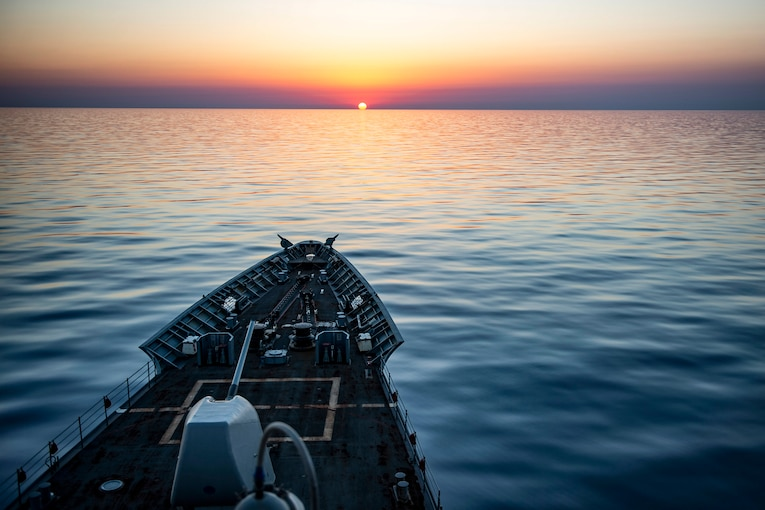 A ship's bow is visible as it travels toward a low sun creating a dramatic orange, pink and purple horizon.