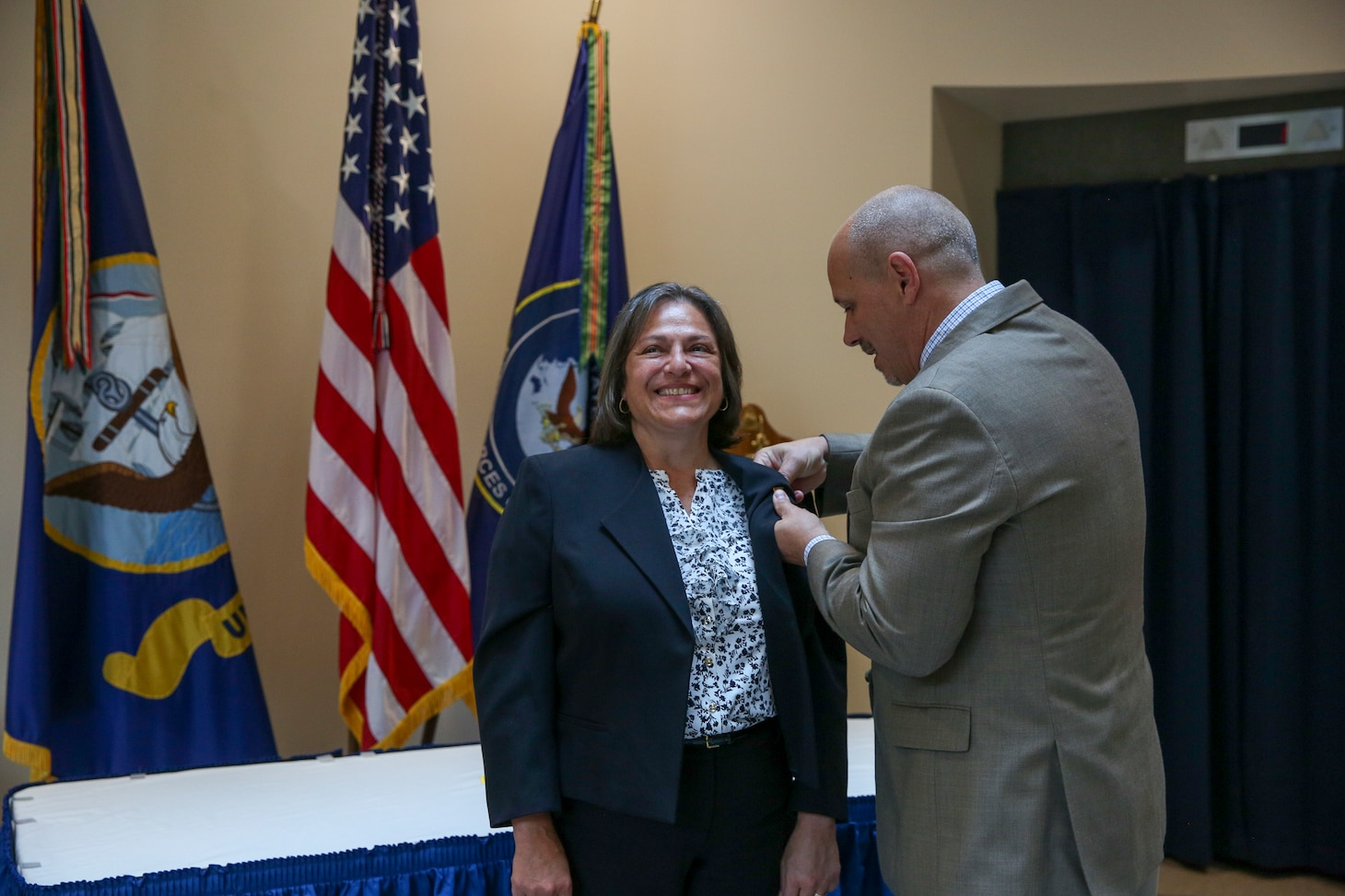 Navy Capt. Tracy Veltre Riker, a native South Brunswick, New Jersey and current resident of Virginia Beach,Virginia, receives the senior executive service (SES) lapel pin from her spouse during her promotion to the position of director, Fleet Installations and Environment Readiness at U.S. Fleet Forces (USFF) Command in Norfolk, Virginia.