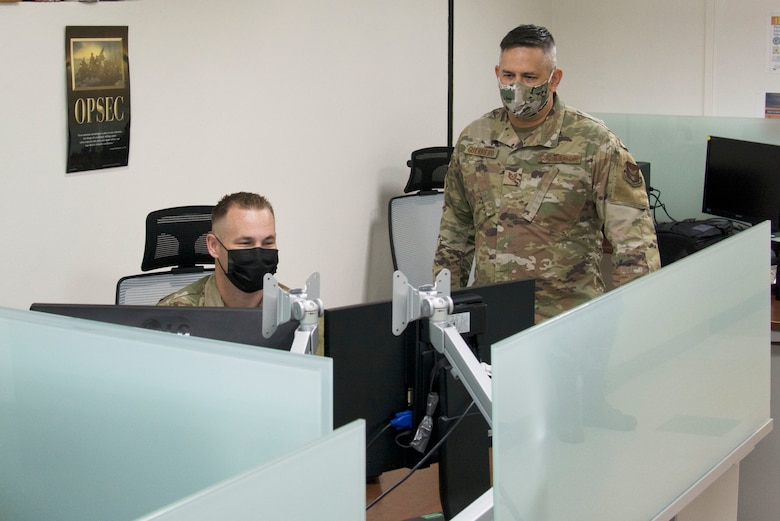 A photo of U.S. Air Force Master Sgt. David Popp, left, and Tech. Sgt. Kerry Guerrero of the 44th Aerial Port Squadron utilize the recently built cybercafe at Andersen Air Force Base, Guam, July 28, 2020. The cybercafe was created to increase internet accessibility by optimizing workspace utilization through the use of squadron innovation funds from AFWERX, the Air Force's innovation program. (U.S. Air Force photo by Tech. Sgt. Tricia C. Topasna)