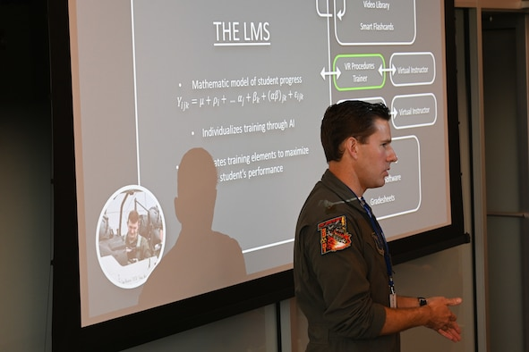 Airman gives a speech in front of a power point presentation.