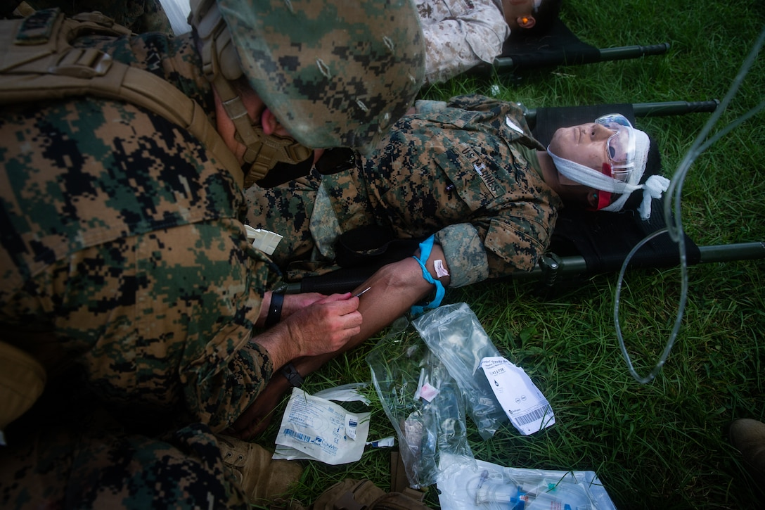 A Navy corpsman with Combat Logistic Battalion (CLB) 31, 31st Marine Expeditionary Unit (MEU), inserts an intravenous therapy into a simulated combat casualty during a nightingale exercise at Camp Hansen, Okinawa, Japan.