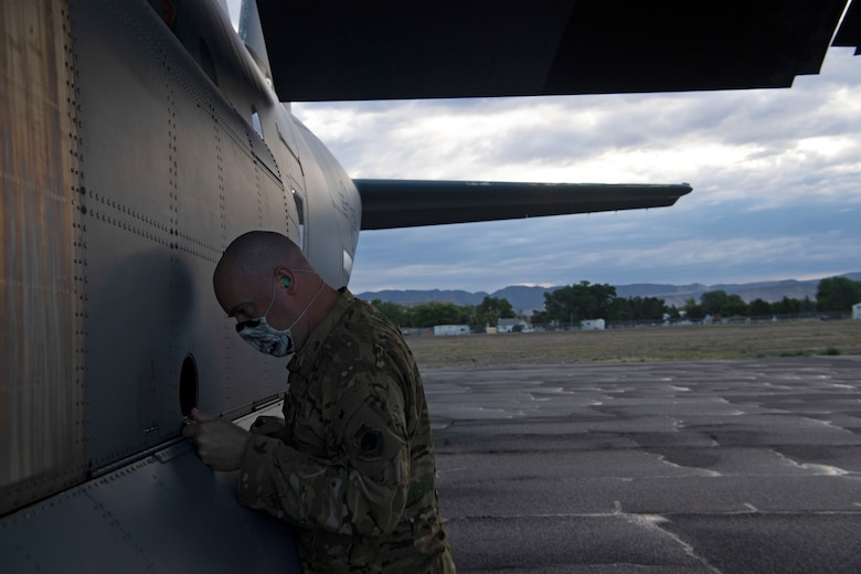 Capt. Matthew Calland, 41st Airlift Squadron chief of tactics, inspects his C-130J Super Hercules prior to flight during pre-deployment training at Montrose Regional Airport, Colo., July 28, 2020. Throughout the training, the 41st AS was able to perform airdrops, offload cargo, fly low-levels, land on dirt runways, integrate with other wings, operate in low-light environments and navigate topography that the squadron is unable to replicate at home station.