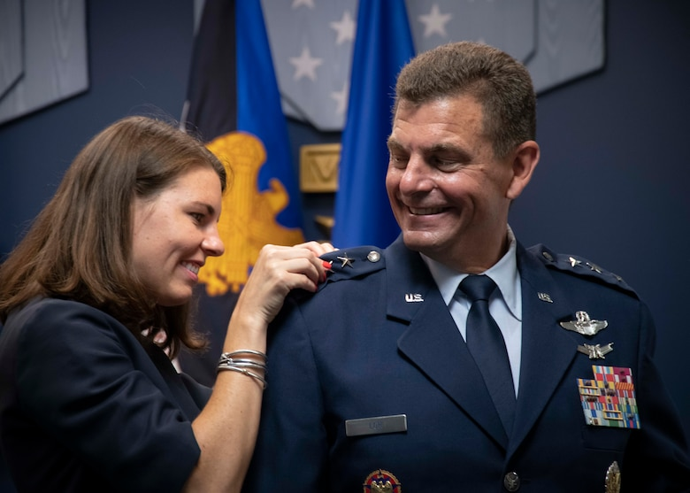 U.S. Air Force Maj. Gen. Michael A. Loh is promoted to the rank of lieutenant general during a Change of Responsibility ceremony at the Pentagon July 28, 2020. Loh's wife, Diane, and daughter, Heather, pinned the new lieutenant general insignia on his service jacket. (U.S. Air National Guard photo by Technical Sgt. Morgan R. Lipinski)