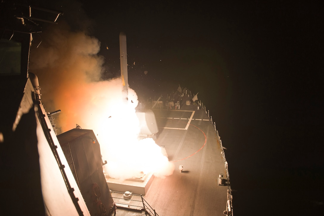 Ship fires missile at night.