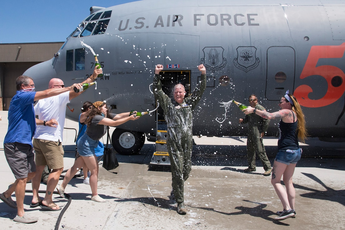 Col. James DeVere, 302nd Airlift Wing commander, steps out of a C-130 aircraft to celebrate with friends and family after his final flight as an Air Force pilot