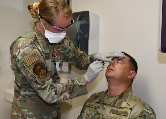 Senior Airman Chelsea Barrow, 22nd Operational Medical Readiness Squadron Independent Duty Medical Technician, administers a COVID-19 test to Master Sgt. Elliott Gossett, 22nd Logistics Readiness Squadron fuels operations section chief, at the flight medical clinic July 17, 2020, at McConnell Air Force Base, Kansas. McConnell initiated testing as an added step in the deployment process to help keep our Airmen safe, thus minimizing the spread of COVID-19 while maintaining mission readiness. (U.S. Air Force photo by Tech. Sgt. Jennifer Stai)