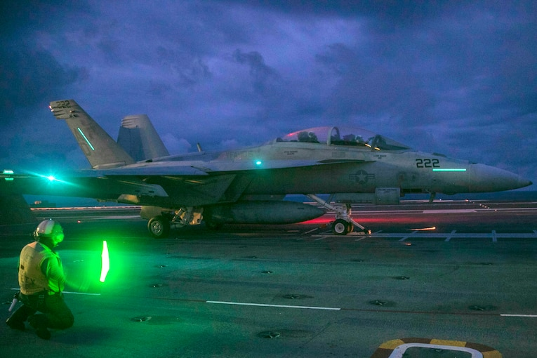 A military fighter jet prepares to launch from an aircraft carrier.