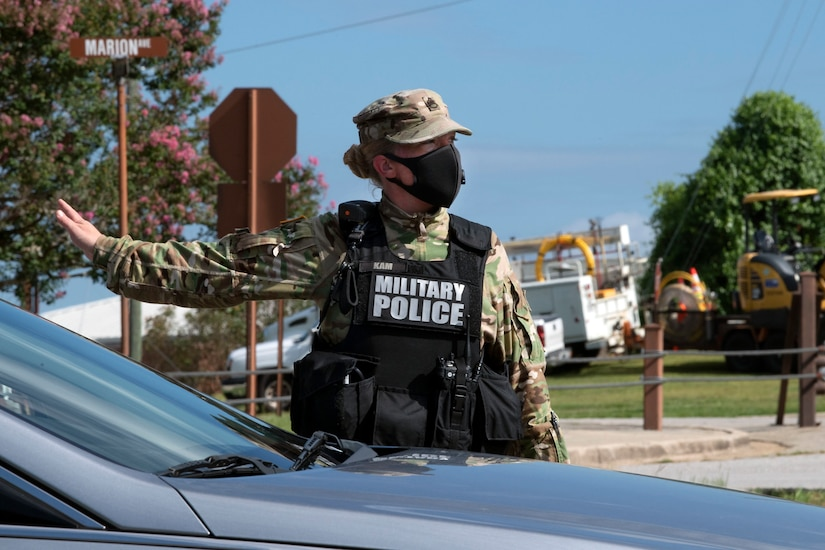 A soldier wearing a face mask and a military police vest directs traffic.