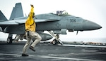 """ARABIAN SEA (July 26, 2020) Lt. Amy Blades-Langjahr, from Casper, Wyo., signals an F/A-18E Super Hornet, from the """"Kestrels"""" of Strike Fighter Squadron (VFA) 137, to launch off from the flight deck of the aircraft carrier USS Nimitz (CVN 68). Nimitz, the flagship of Nimitz Carrier Strike Group, is deployed to the U.S. 5th Fleet area of operations to ensure maritime stability and security in the Central Region, connecting the Mediterranean and Pacific through the Western Indian Ocean and three critical chokepoints to the free flow of global commerce. (U.S. Navy photo by Mass Communication Specialist 3rd Class Sarah Christoph/Released)"""