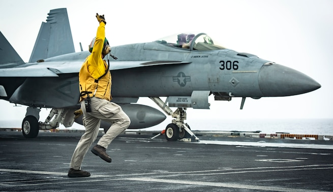 "ARABIAN SEA (July 26, 2020) Lt. Amy Blades-Langjahr, from Casper, Wyo., signals an F/A-18E Super Hornet, from the ""Kestrels"" of Strike Fighter Squadron (VFA) 137, to launch off from the flight deck of the aircraft carrier USS Nimitz (CVN 68). Nimitz, the flagship of Nimitz Carrier Strike Group, is deployed to the U.S. 5th Fleet area of operations to ensure maritime stability and security in the Central Region, connecting the Mediterranean and Pacific through the Western Indian Ocean and three critical chokepoints to the free flow of global commerce. (U.S. Navy photo by Mass Communication Specialist 3rd Class Sarah Christoph/Released)"