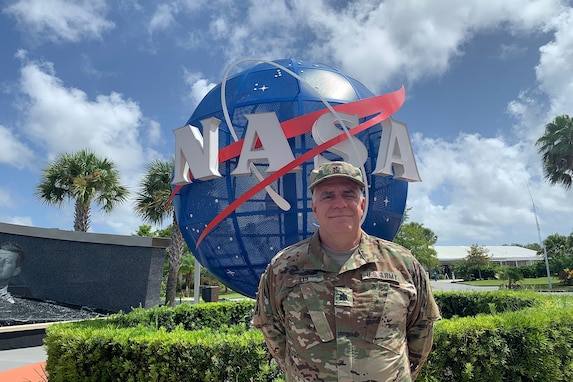U.S. Army Reserve Lt. Col. Pat Lis pauses for a photo at the entrance to the Kennedy Space Center Visitor Complex in Florida.