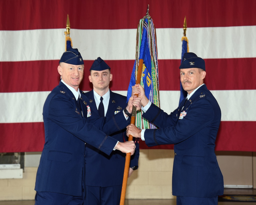 Col. Seth Graham, 14th Flying Training Wing commander, hands Col. Justin Spears, 14th Operations Group commander, the 14th OG guidon at the 14th OG change of command ceremony on July 24, 2020, at Columbus Air Force Base, Miss. The 14th Operations Group and its six squadrons are responsible for the 52-week Specialized Undergraduate Pilot Training (SUPT) mission at Columbus. The group also performs quality assurance for contract aircraft maintenance. (U.S. Air Force photo by Elizabeth Owens)