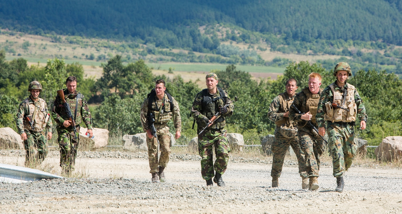 Seven uniformed personnel, many with rifles, walk together on a gravel road.